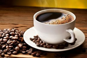 Hot cup of coffee with coffee beans