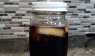 mason jar with straw, ice and cold brew coffee on a countertop