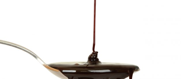 chocolate syrup dripping from a spoon